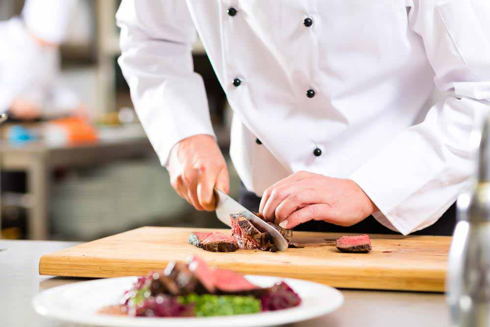 A chef carving and slicing cooked meat with a knife in a cutting board